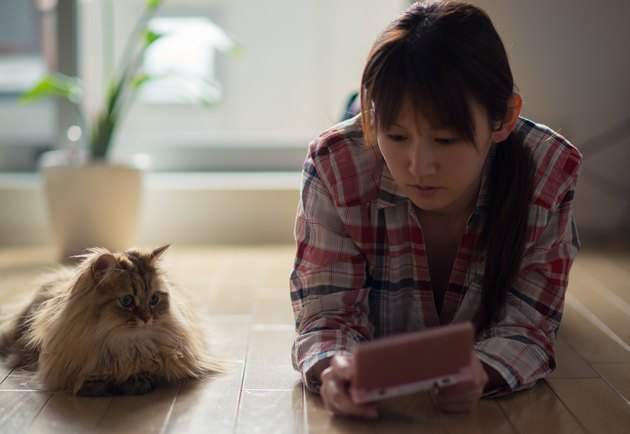 woman playing video game on the floor next to her cat