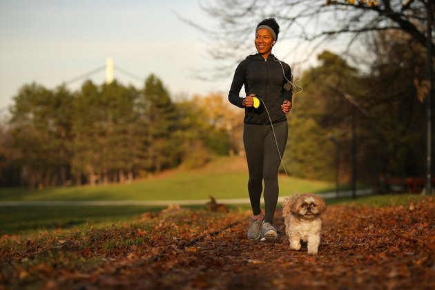 Happy black athletic woman running with a dog at the park.