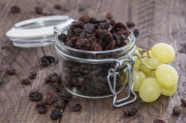 raisins in a jar next to grapes