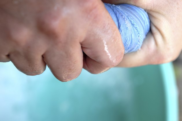 Close-up of a person's hand squeezing a cloth