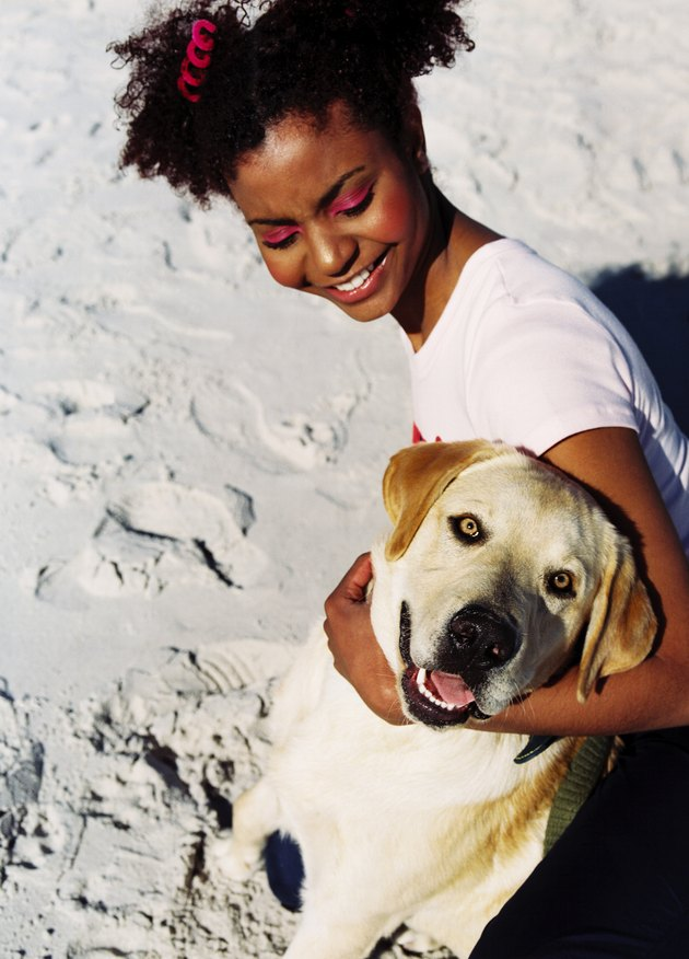young woman on the beach holding dog