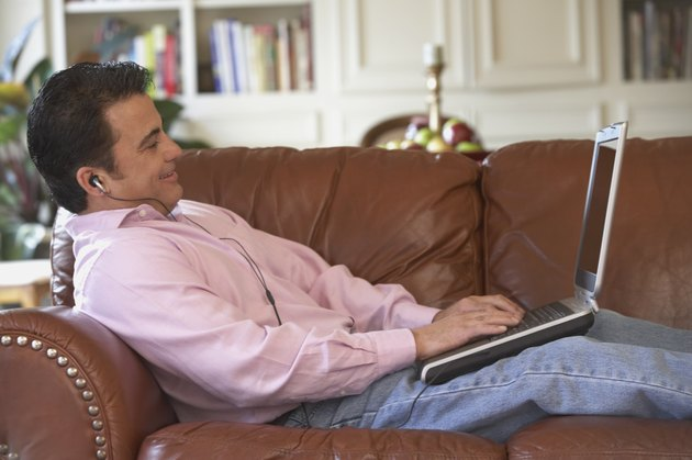 Side profile of a mid adult man lying on a couch working on a laptop