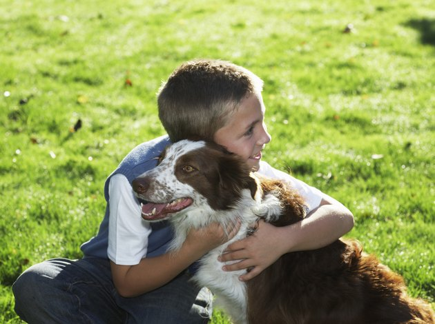 Boy (7-9) hugging dog, smiling