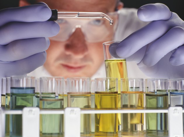 Chemist dropping liquid into test tubes, close-up