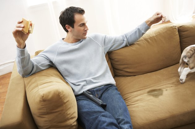Man sitting on sofa by dog walking away from wet patch