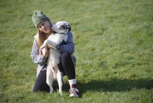 Girl (8-9) crouching in park hugging dog