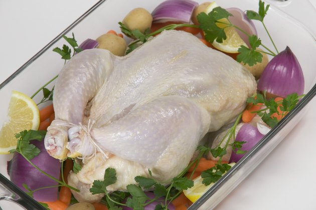 Uncooked chicken on a bed of vegetables