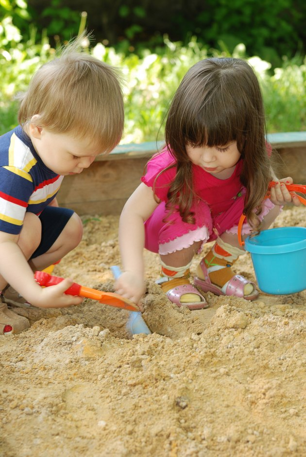 The boy and girl playing to a sandbox