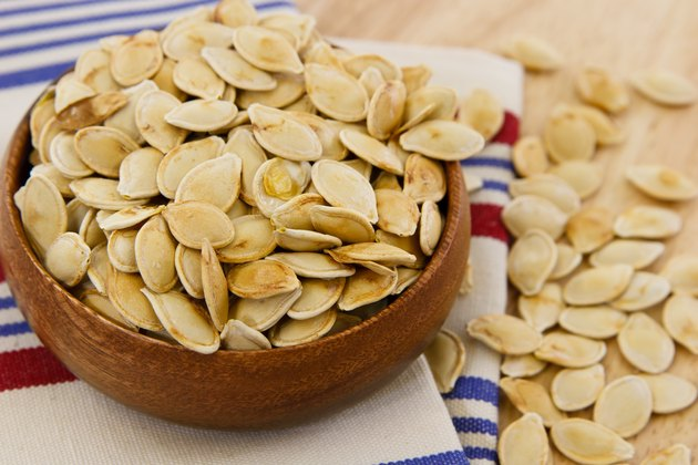 Toasted pumpkin seeds overflowing a wooden bowl