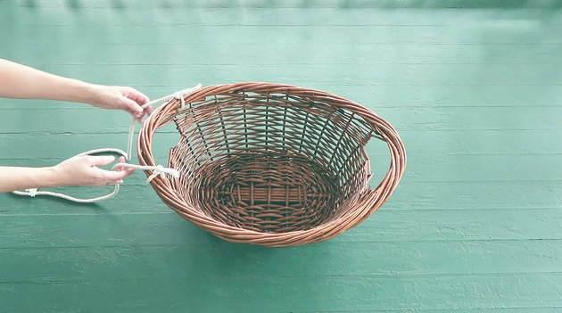 Tying two strands of rope to one side of the basket