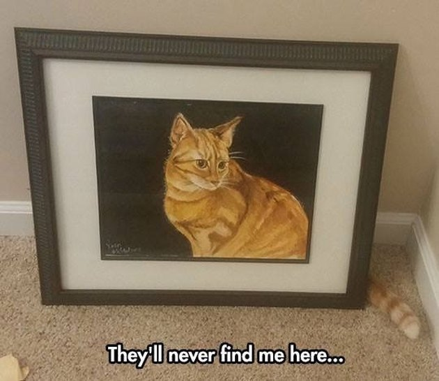 Cat hiding behind painting of cat. Caption: They'll never find me here.