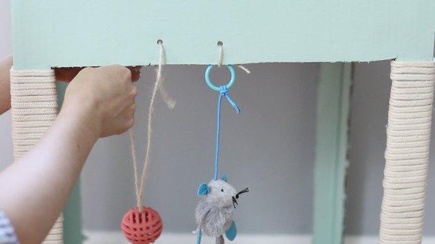 tying cat toys to box