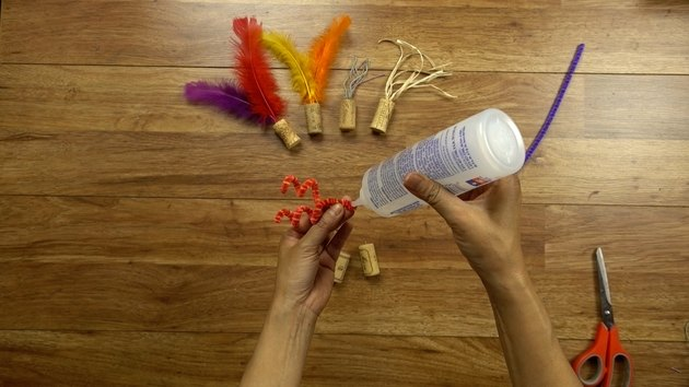 Gluing pipe cleaner for DIY cat toys out of wine corks.