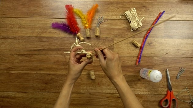 Inserting raffia for DIY cat toys out of wine corks.