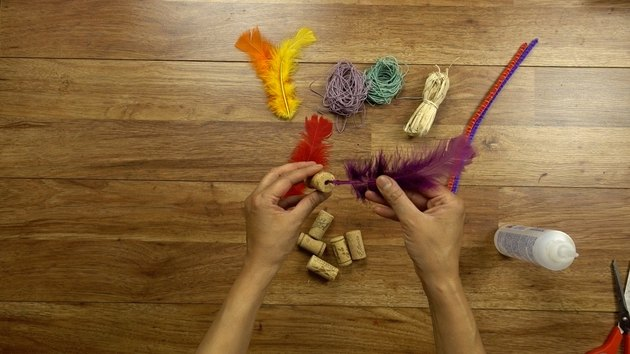 Gluing feather for DIY cat toys out of wine corks.