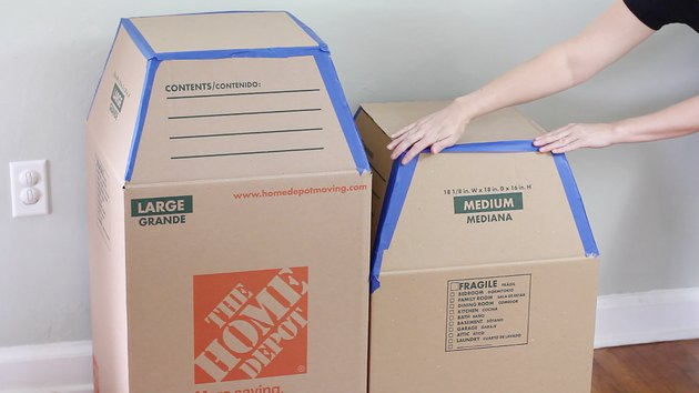 Taping scrap cardboard on top of boxes