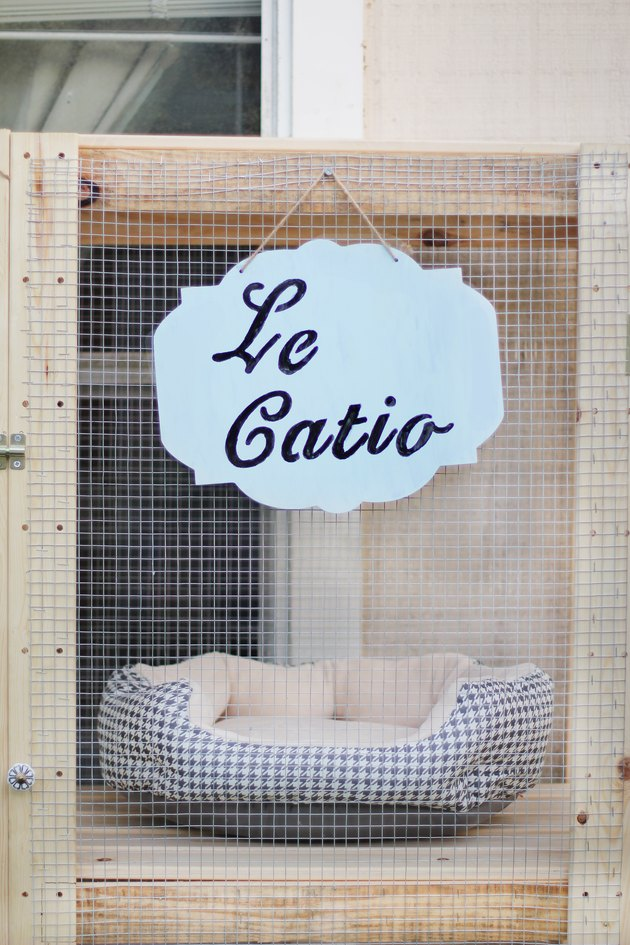 """Le Catio"" sign hanging on front of catio"