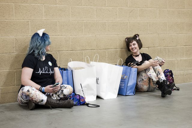 Two women relax against the wall at CatCon 2018.