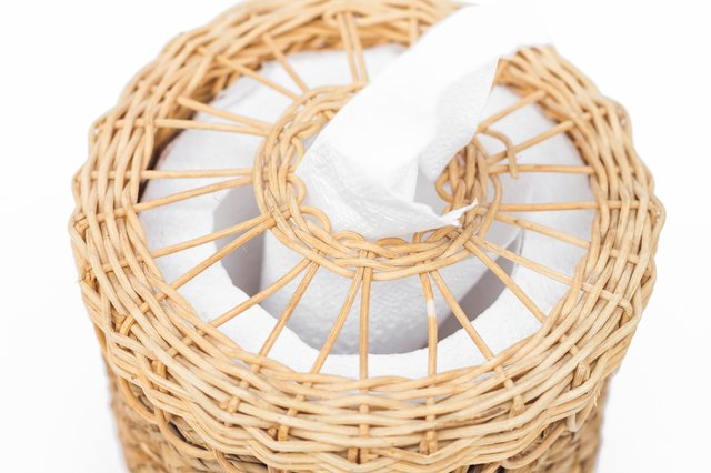 Close-Up Of Tissue Paper In Wicker Basket Against White Background