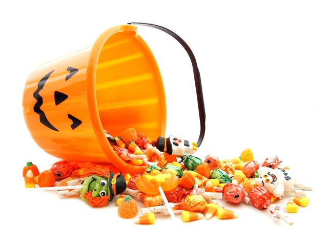 A jack-o-lantern bucket full of candy tipped over